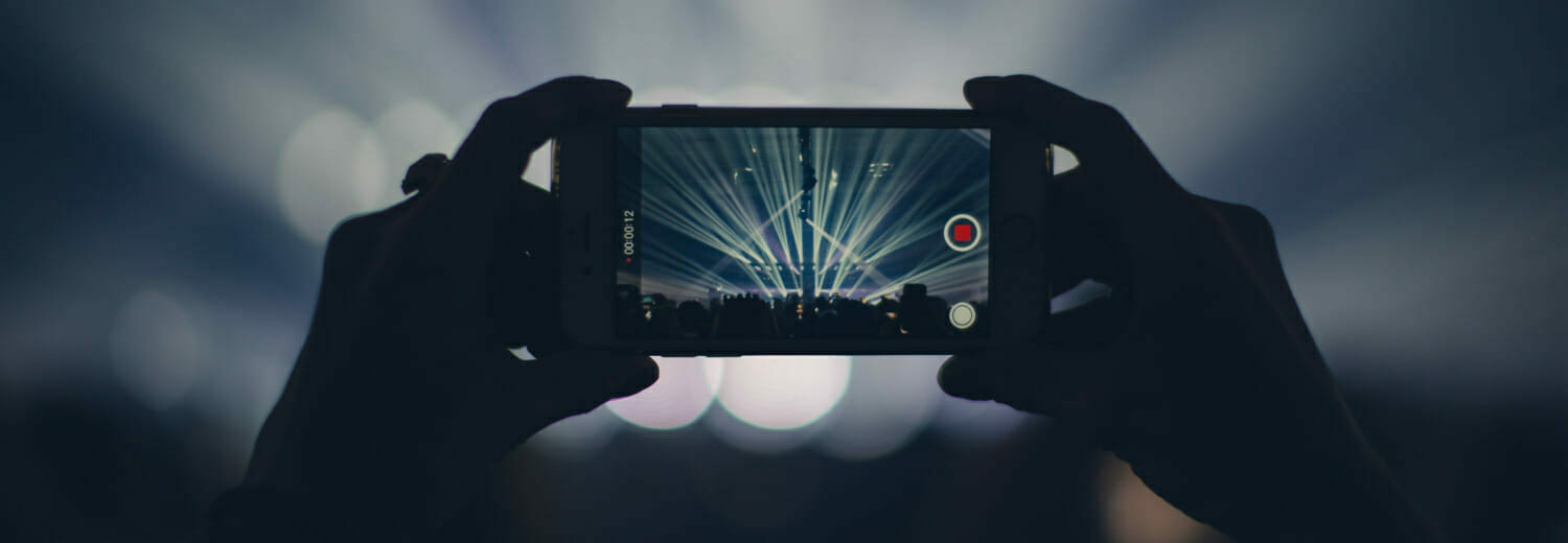 Person holding iPhone at concert to record video