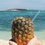 Pineapple drink held up in front of the beach