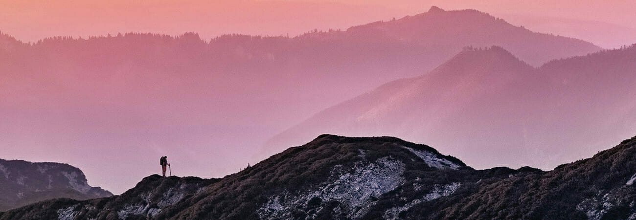 Person hiking on mountain against pinkish sky