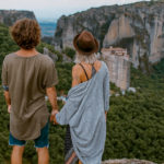 Couple standing on mountain top staring into distance