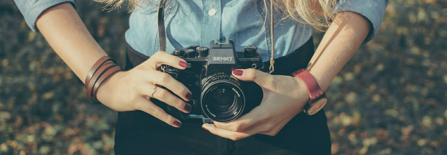 Close up of a woman's hands holding a camera