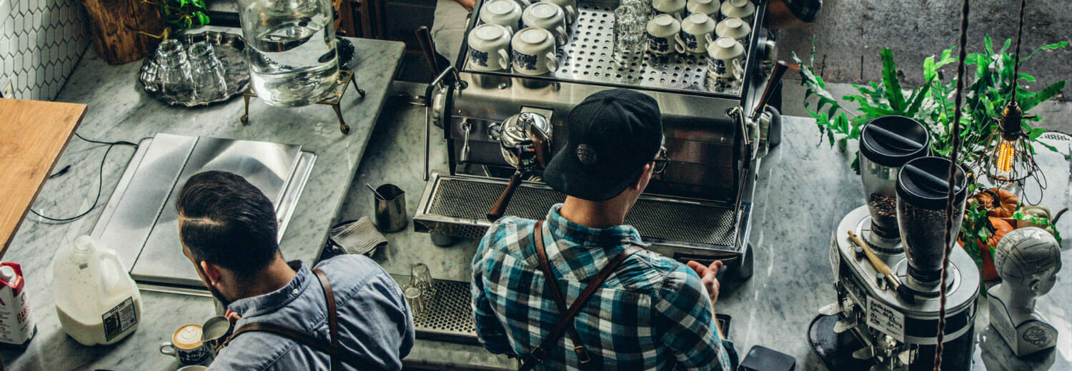 2 Baristas at work in cafe, making coffee