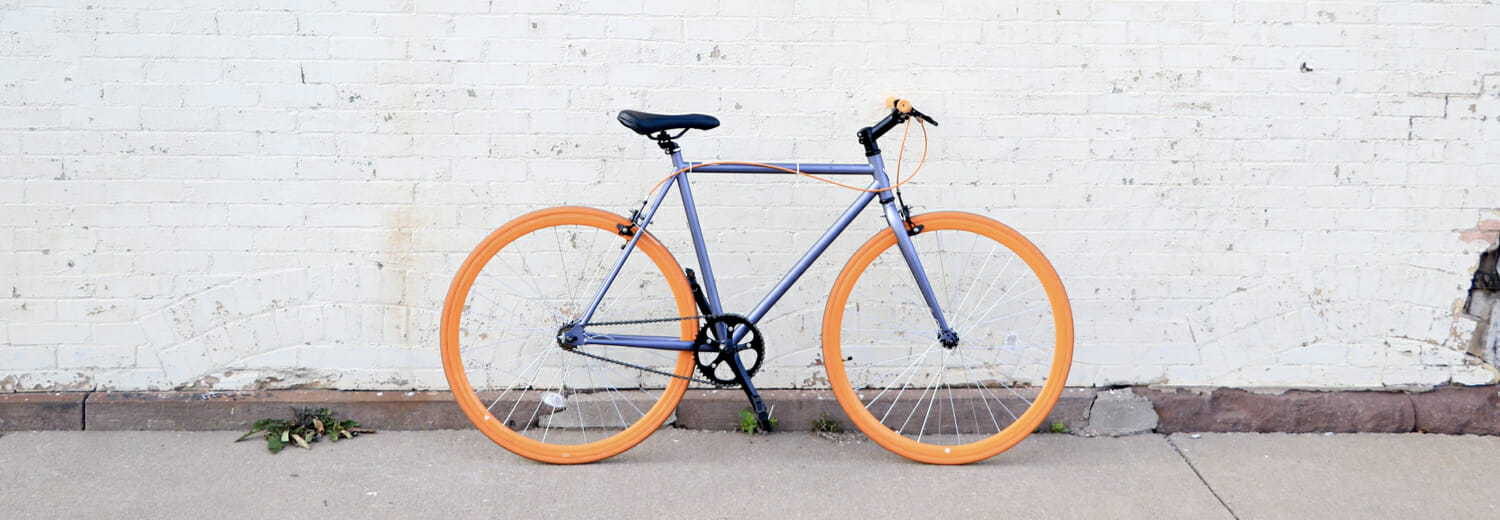 Light purple icycle with orange tires in front of a light grey brick wall