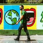 Man walking down street beside colorful street art