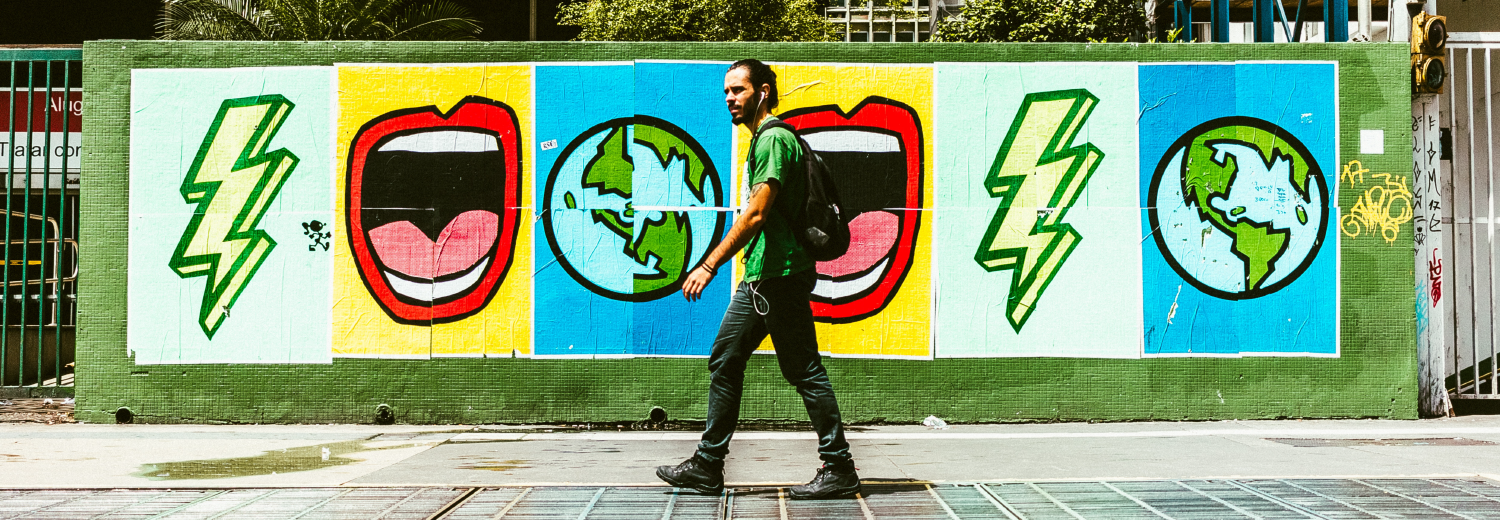 Man walking down street beside colorful street art