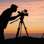 Person with camera on tripod on hill at sunset