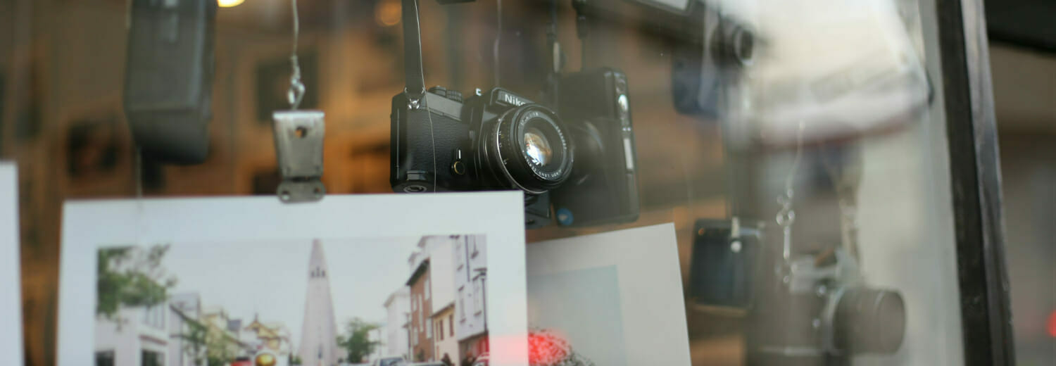 Photography prints and cameras on display in shop window