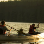 Family canoeing down a river at dusk