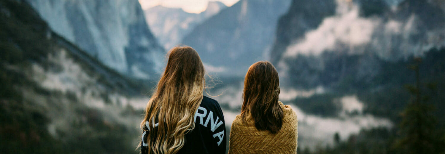 Backs of two women in mountains staring out