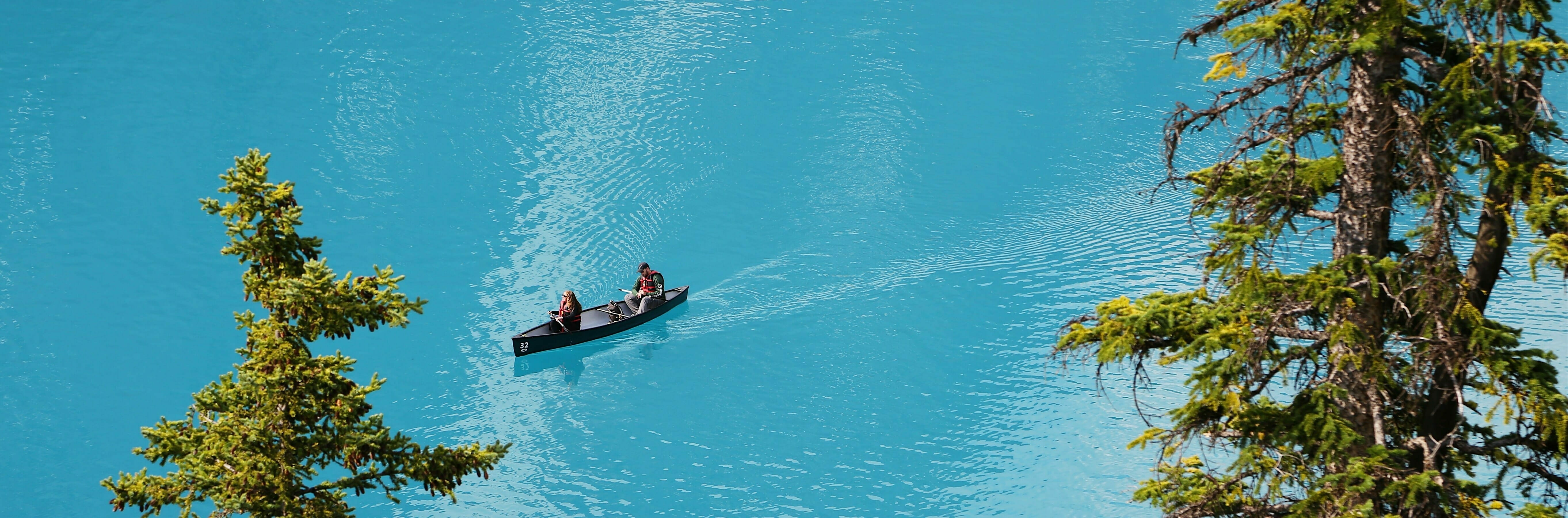 Overhead shot of People canoeing on bright blue lake
