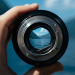 Close up shot looking into the opening of a camera lens onto a lake with surrounding mountains and blue sky