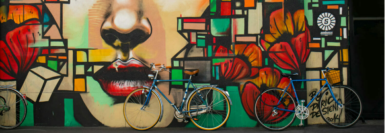 Bikes leaning up against a colourful graffiti wall