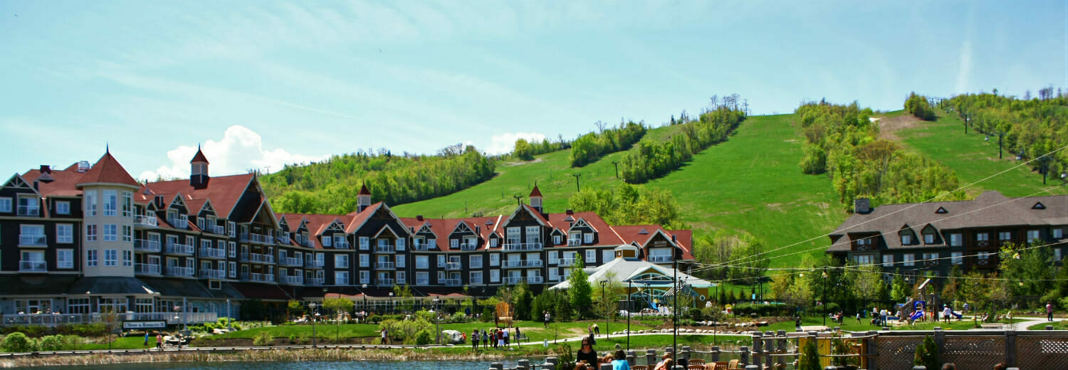 Blue Mountain village in the summertime. View of village, hotels, and grassy hill.
