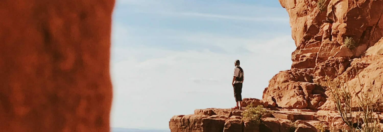Man on mountain in desert staring out into the distance