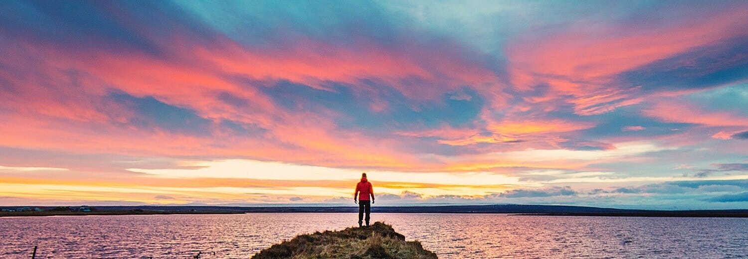 Man in a red jacket standing on a rock gazing into a pink sunset