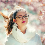 Girl wearing glasses with cherry blossoms in the background