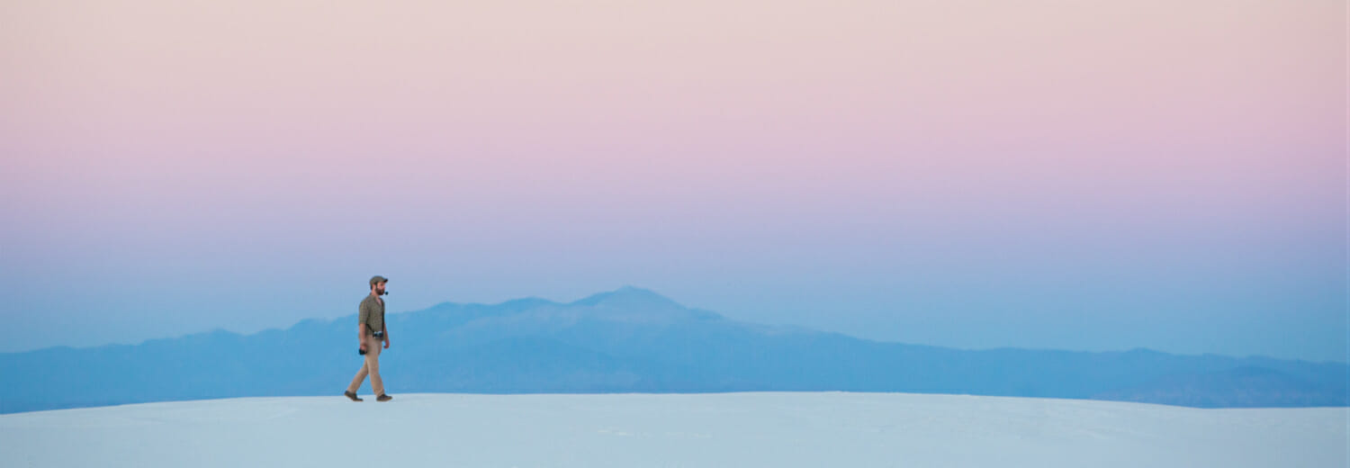 Man walking across White Sands, US, against pinkish sky