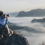 Man taking photo on edge of mountain above the clouds