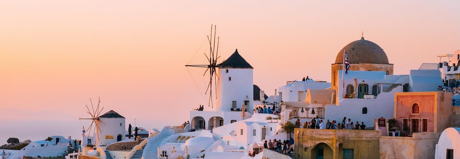 Greek Island white houses set against a pink and orange sunset
