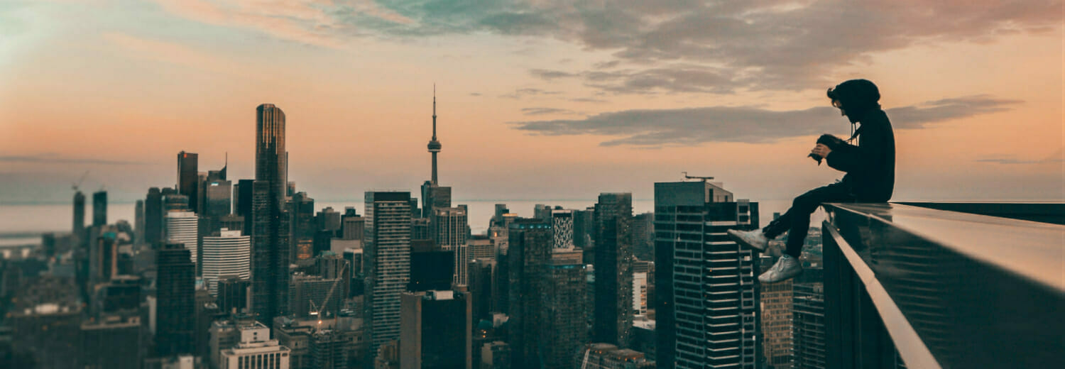 Man on top of building with camera, taking photos of Toronto skyline