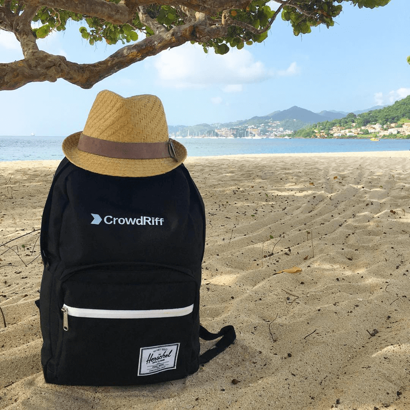 CrowdRiff branded backpack, in the sand on a beach, with a sun hat on top