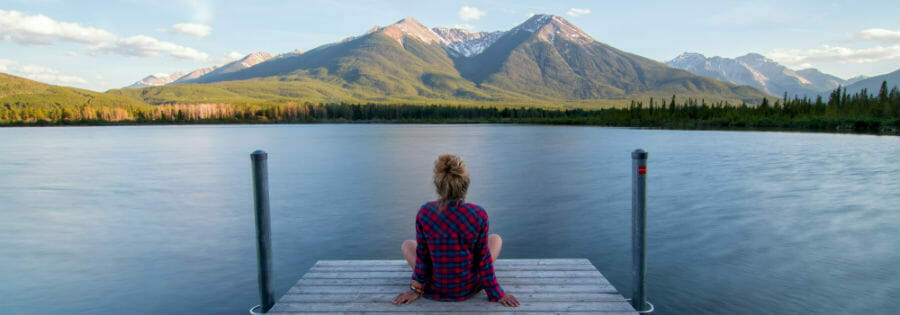 Girl sitting on dock on lake in the mountains